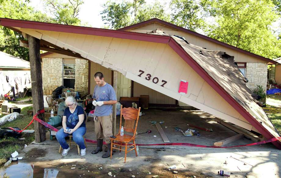 Kim Morris and her son, Robert Morris, take a break from cleaning Robert's home on South Pleasant Valley Road in Austin, Texas, on Friday Nov. 1, 2013, a day after a flood destroyed the house and his belongings. (AP Photo/Austin American-Statesman, Jay Janner) AUSTIN CHRONICLE OUT, COMMUNITY IMPACT OUT, MAGS OUT; NO SALES; INTERNET AND TV MUST CREDIT PHOTOGRAPHER AND STATESMAN.COM Photo: Jay Janner, MBO / Austin American-Statesman