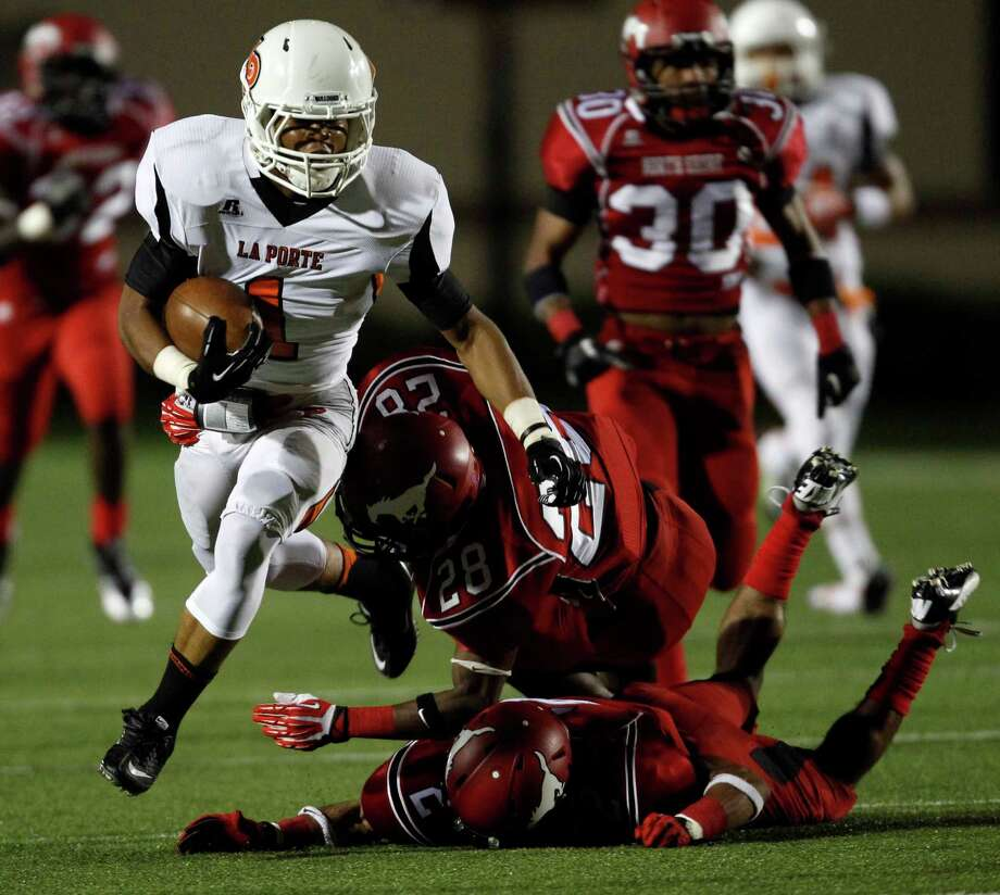 La Porte's Victor Holmes (1) escapes the tackle of North Shore's Darius Mouton (28) and Kevin DeLeon during the first half of a high school football game, Friday, November 1, 2013 at Galena Park ISD Stadium in Houston. Photo: Eric Christian Smith, For The Chronicle