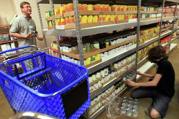 Volunteers Tracy Wood and Sky Bradley sort food on Thursday at the Second Mile Mission food pantry, which stays open late weekdays and weekends to accommodate working families in Missouri City.