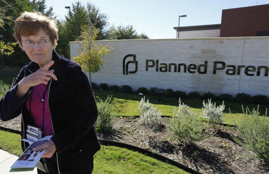 Marian Honquest holds materials offering abortion alternatives on the sidewalk Friday in front of Planned Parenthood in Fort Worth. Photo: Photos By David Kent / Associated Press