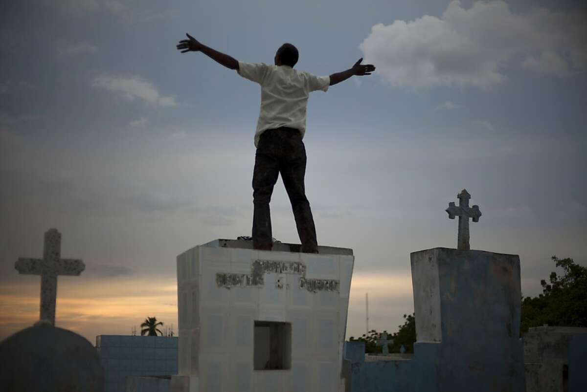 A Voodoo devotee prays on top of a grave stone during Day of the Dead celebrations at the cemetery in Port-au-Prince, Haiti. Friday, Nov. 1, 2013. Devotees of Voodoo honor the Gede as well as their dead relatives by wearing white, black or purple and by making offerings of candles, food and alcohol at cemeteries on Nov. 1 and 2.