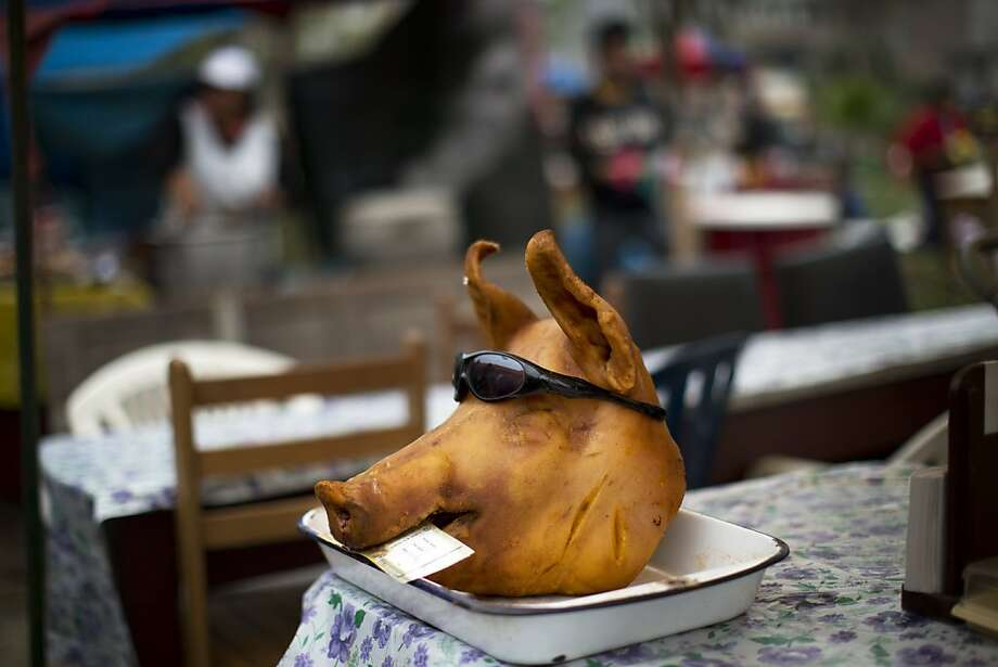 A pig's head donning a pair of sunglasses is used to promote a makeshift restaurant near the Nueva Esperanza cemetery, as part of the Day of the Dead celebrations in Lima, Peru, Friday, Nov. 1, 2013. The souls of departed loved ones are being honored around Latin America as celebrants blend pre-Columbian rituals with the Roman Catholic observance of all Saint's Day on Nov. 1 and All Soul's Day on Nov. 2 to mark the Day of the Dead. Photo: Rodrigo Abd, Associated Press