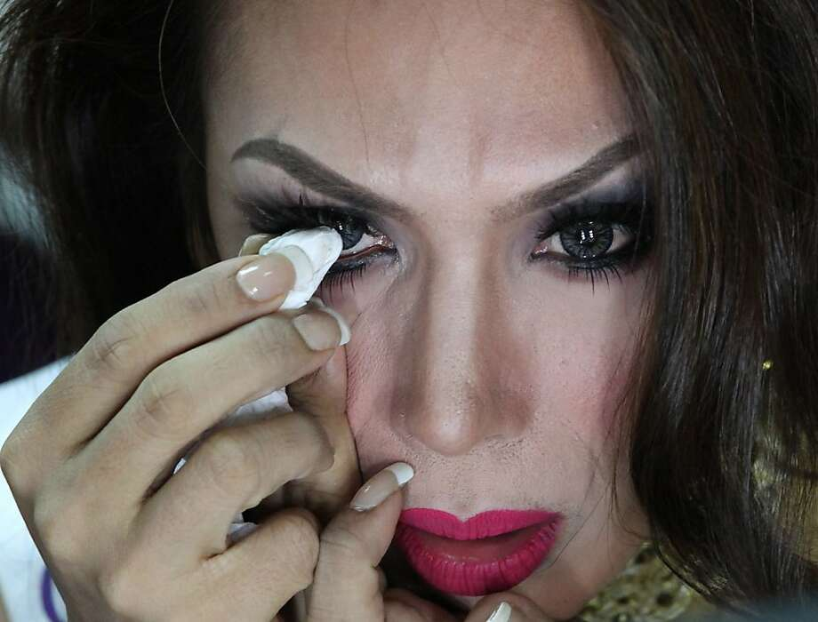 Andrea Justine Aliman of the Philippines applies makeup on her eye during a backstage photo session at the Miss International Queen 2013 transvestite beauty pageant in Pattaya, southeastern Thailand Friday, Nov. 1, 2013. Twenty-five contestants from 17 countries participate in this year's pageant which has been held for nine respective years.  Photo: Apichart Weerawong, Associated Press