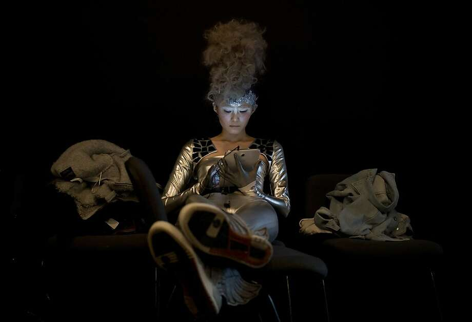 A model with a hairstyle created by Chinese hairstylist Wu Jia plays a tablet computer as she prepares for the L'Oreal Hairstyling Show at China Fashion Week in Beijing Friday, Nov. 1, 2013.  Photo: Andy Wong, Associated Press