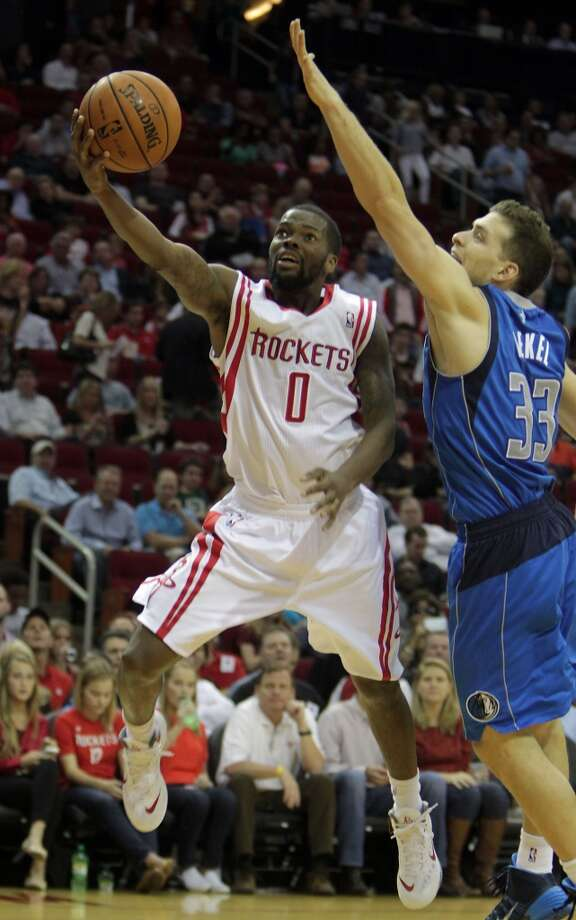 Rockets point guard Aaron Brooks left, shoots the ball over the Mavericks point guard Gal Mekel. Photo: James Nielsen, Houston Chronicle