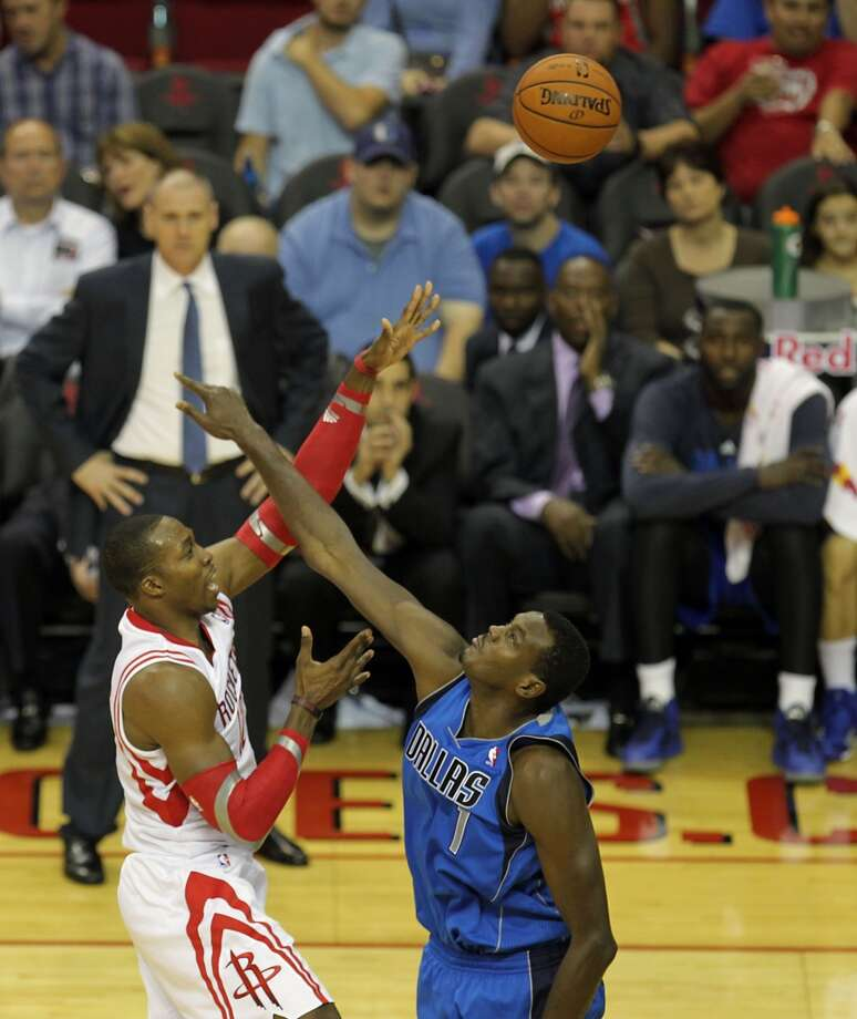 Rockets center Dwight Howard left, shoots the ball over Mavericks center Samuel Dalembert. Photo: James Nielsen, Houston Chronicle