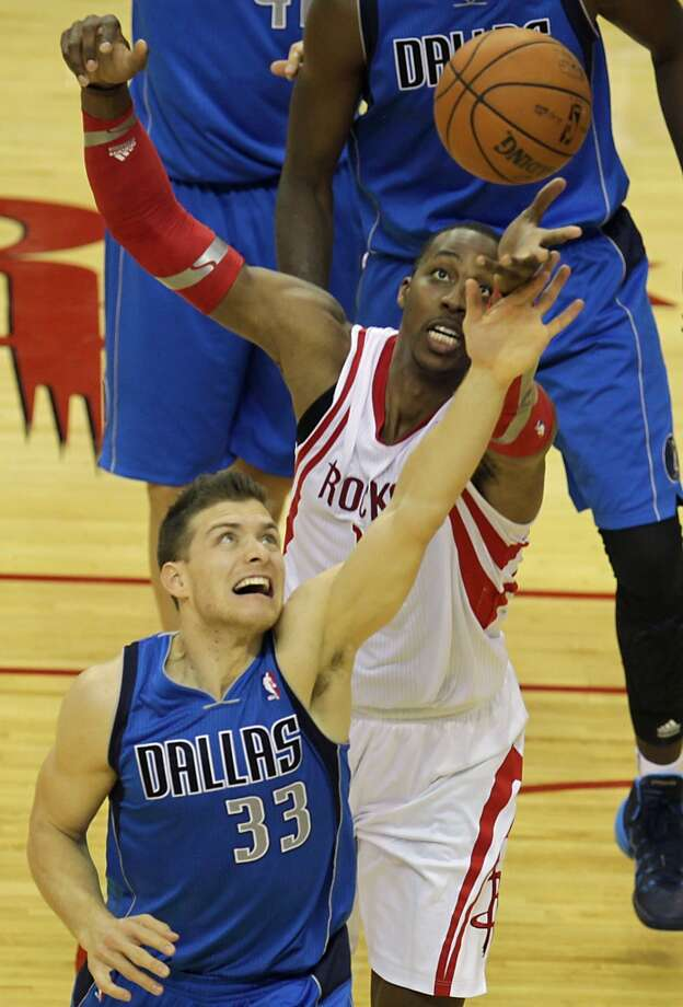 Mavericks point guard Gal Mekel left, and Rockets center Dwight Howard right, jump for a loose ball. Photo: James Nielsen, Houston Chronicle
