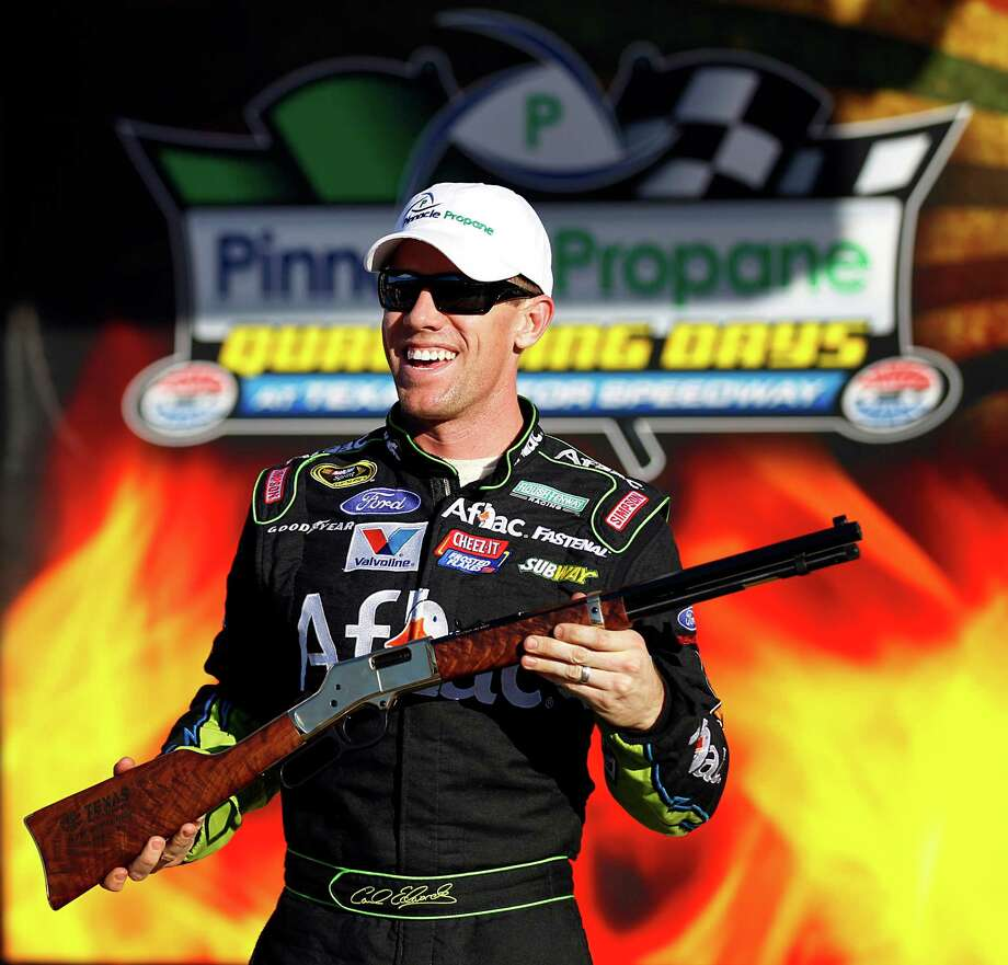 Carl Edwards gets a kick out of his prize for claiming the pole for Sunday's race at Texas Motor Speedway. Photo: Tom Fox, MBR / The Dallas Morning News
