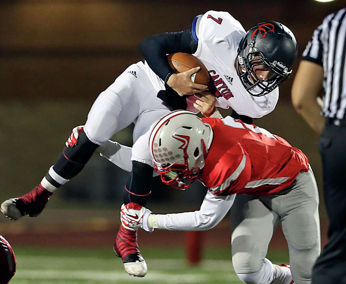 Cougar quarterback Philip Shelton is upended by linebacker Shawn Calvin as Judson hosts Canyon at Rutledge Stadium on November 1, 2013.