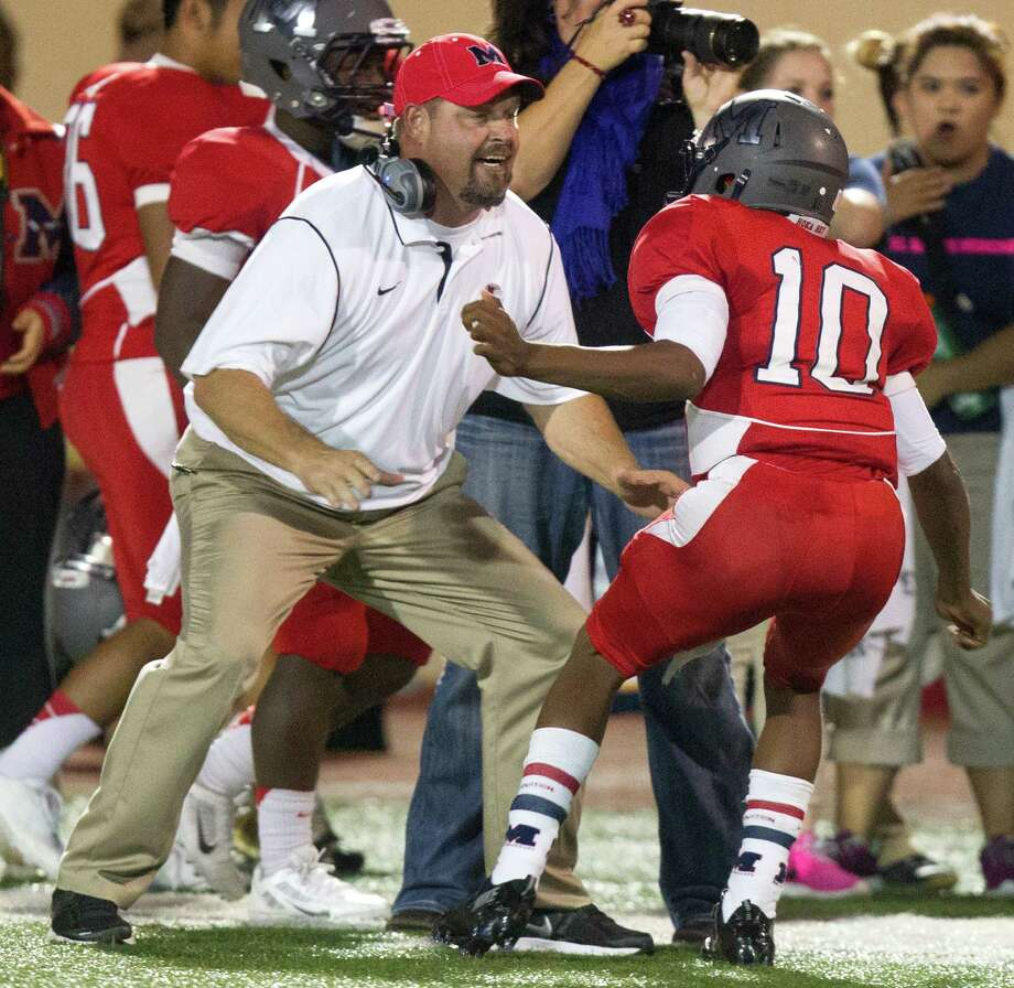 Manvel head coach Kirk Martin celebrates a touchdown with quarterback Deriq King (10) during the second half of a high school football game against Pearland at Alvin Memorial Stadium on Friday, Nov. 1, 2013, in Alvin. Photo: J. Patric Schneider, For The Chronicle / © 2013 Houston Chronicle