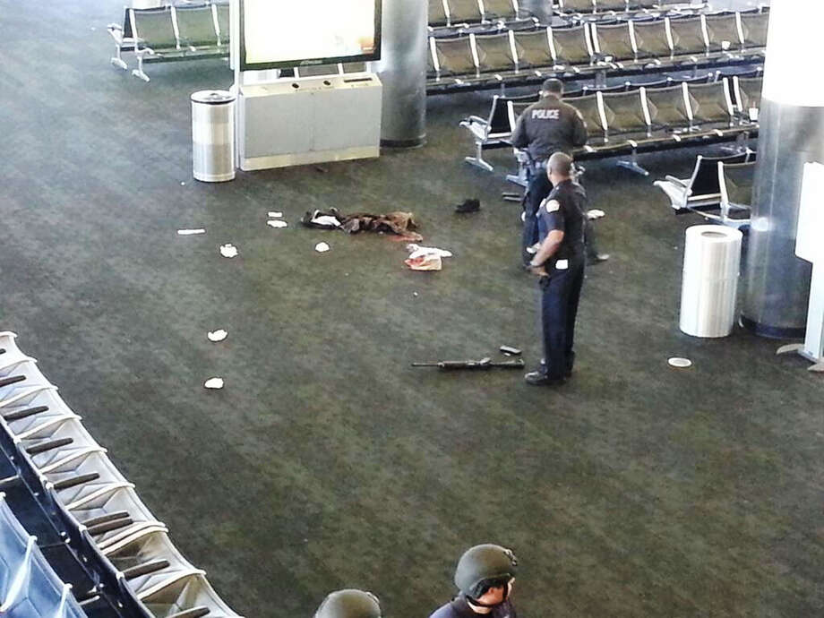 In this photo provided to the AP, which has been authenticated based on its contents and other AP reporting, police officers stand near an unidentified weapon in Terminal 3 of the Los Angeles International Airport on Friday, Nov. 1, 2013. Officials said a gunman who opened fire in the terminal was wounded in a shootout with police and taken into custody. (AP Photo) Photo: STR / AP