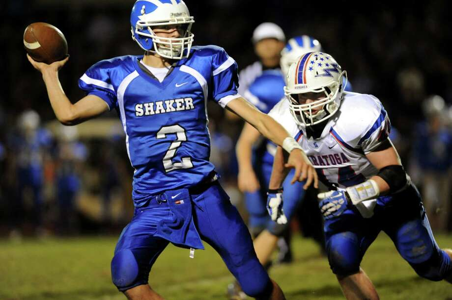 Shaker's quarterback Matt Woods, left, gets pressure from Saratoga's Nick Stiansen during their Class AA semifinal football game on Friday, Nov. 1, 2013, at Shaker High in Latham, N.Y. (Cindy Schultz / Times Union) Photo: Cindy Schultz / 00024468A