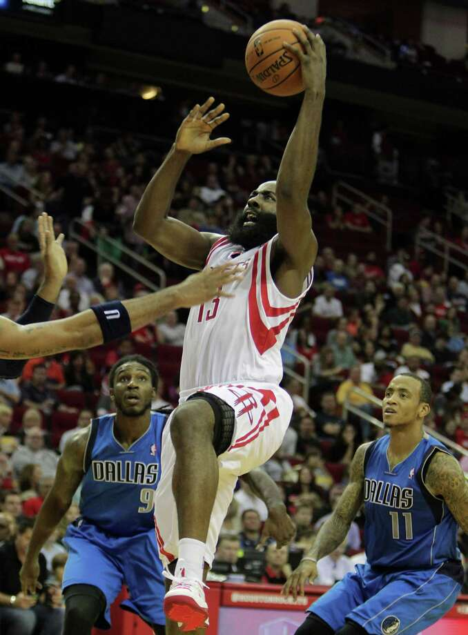 James Harden splits the Mavericks' defense en route to two of his game-high 34 points during second-quarter action at Toyota Center on Friday night. Photo: James Nielsen, Staff / © 2013  Houston Chronicle