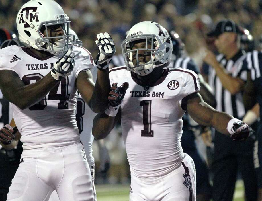 """Running back Ben Malena (right), with receiver Malcome Kennedy, called A&M's four fumbles in a 56-24 rout of Vanderbilt last week a """"freak deal."""" Photo: Rogelio V. Solis / Associated Press"""