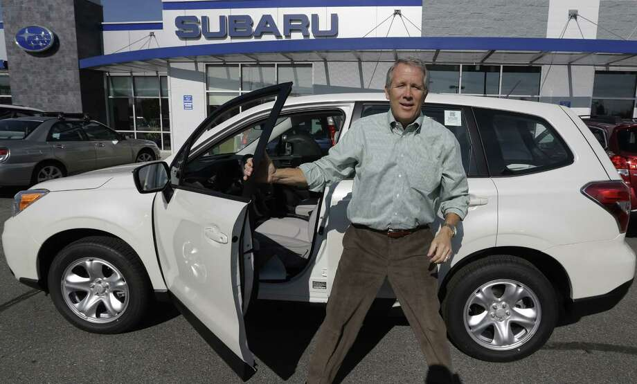 In this Friday, Oct. 25, 2013 photo, Kirk Schneider, who owns Nate Wade Subaru in Salt Lake City, stands by a Subaru Forester at his dealership, in Salt Lake City. Subaru introduced the reworked Forester in the spring. It's bigger inside and gets better gas mileage, so it appeals to baby boomers and families as well as traditional buyers, said Schneider. It was Subaru's top-selling vehicle last month. U.S. sales are up 50 percent this year to more than 84,000. (AP Photo/Rick Bowmer) Photo: Rick Bowmer, STF / AP
