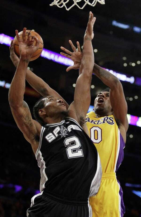 Spurs small forward Kawhi Leonard (left) defends Lakers guard Nick Young during the first quarter. Photo: Alex Gallardo / Associated Press