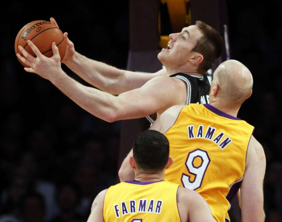 San Antonio Spurs forward Aron Baynes, center, of Australia, shoots with Los Angeles Lakers center Chris Kaman (9) and Lakers guard Jordan Farmar, below, defending in the first quarter during an NBA basketball game Friday, Nov. 1, 2013, in Los Angeles. Photo: Alex Gallardo, Associated Press