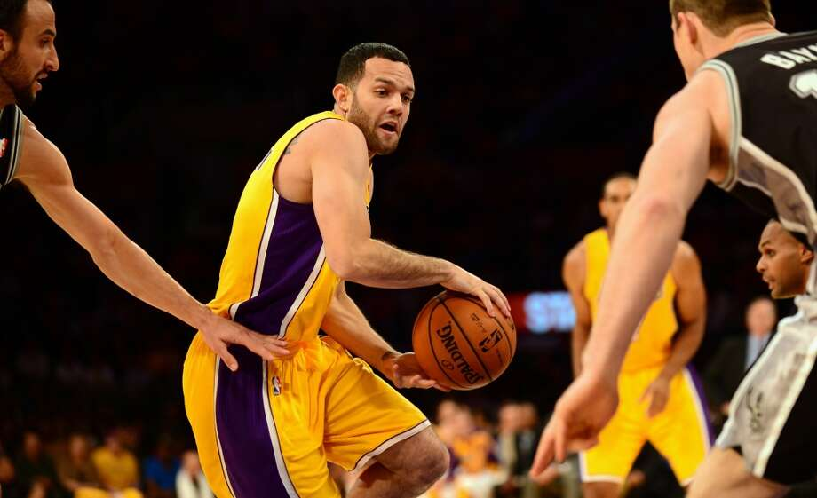 Jordan Farmar of the Los Angeles Lakers prepares a back handed pass under pressure from Manu Ginobilli (L) and Tiago Splitter (R) of the San Antonio Spurs during NBA action on November 1, 2013 in Los Angeles, California. Photo: FREDERIC J. BROWN, AFP/Getty Images
