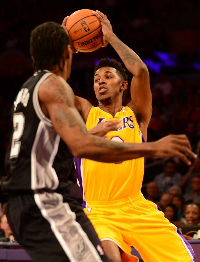 Nick Young of the Los Angeles Lakers looks to pass under pressure from Kawhi Leonard of the San Antonio Spurs (L) during NBA action on November 1, 2013 in Los Angeles, California. Photo: FREDERIC J. BROWN, AFP/Getty Images