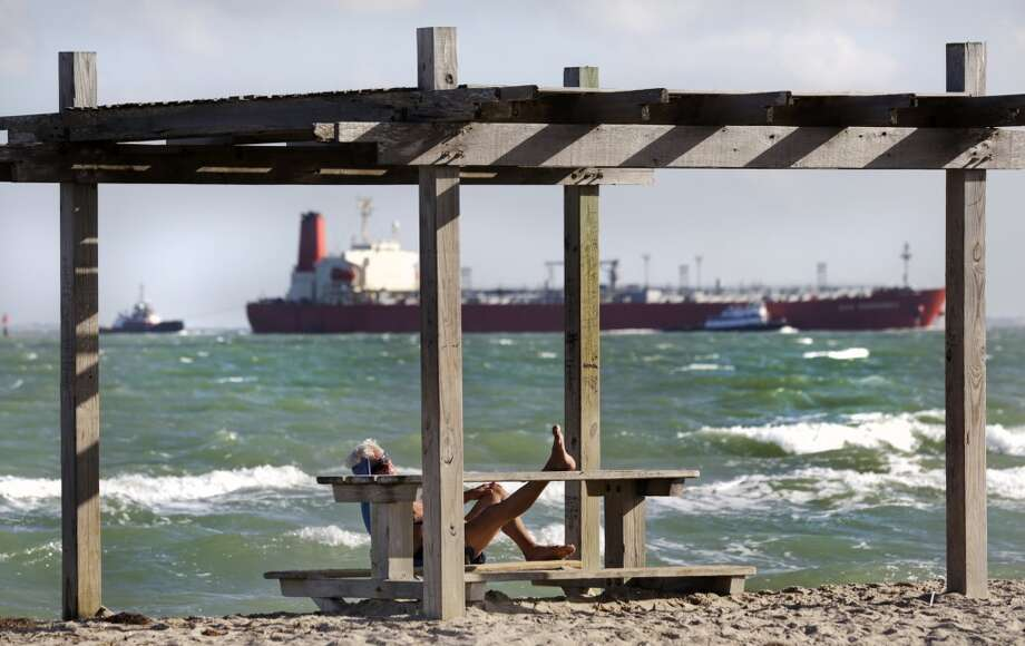 A man rests with his feet propped up at a picnic table on North Beach in Corpus Christi, Monday, Oct. 28, 2013, as a full tanker ship made its way to the shipping channel of Port Corpus Christi. Photo: Bob Owen, San Antonio Express-News