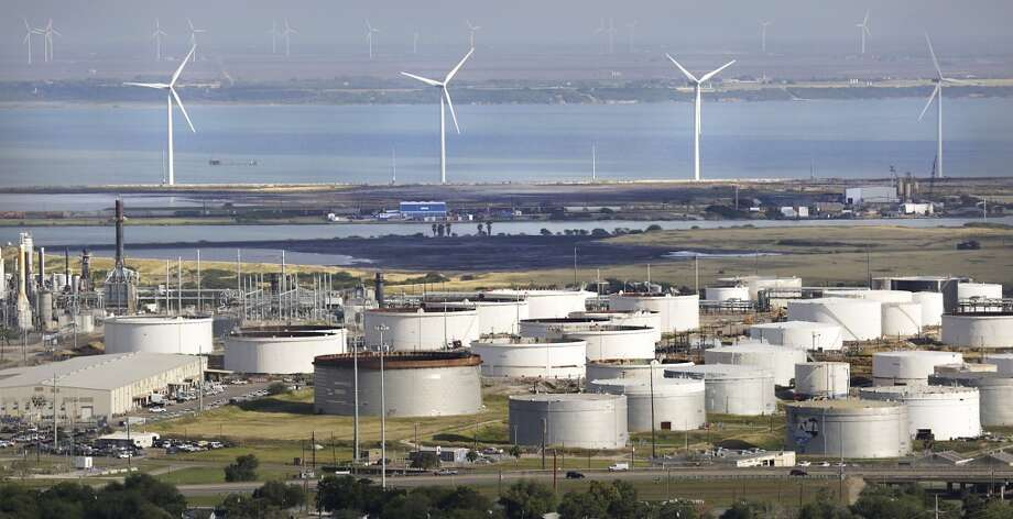 Wind turbines stand near the Citco crude oil storage tanks near the Port Corpus Christi. A larger wind farm can be seen in the distance past Nueces Bay. Photo: Bob Owen, San Antonio Express-News