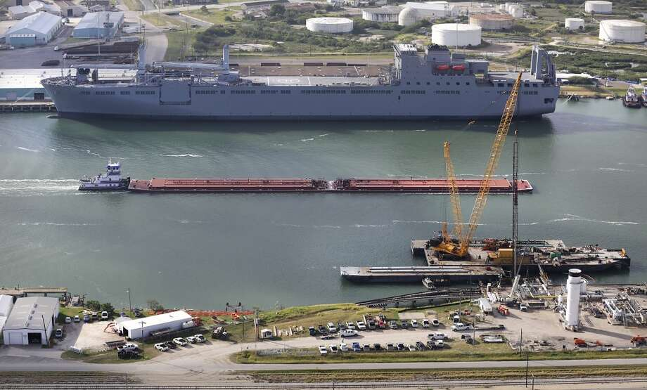A tug boat pushes a barge for oil in the shipping channel past a military transport ship at the Port Corpus Christi. At right is construction on the new NuStar dock. Photo: Bob Owen, San Antonio Express-News