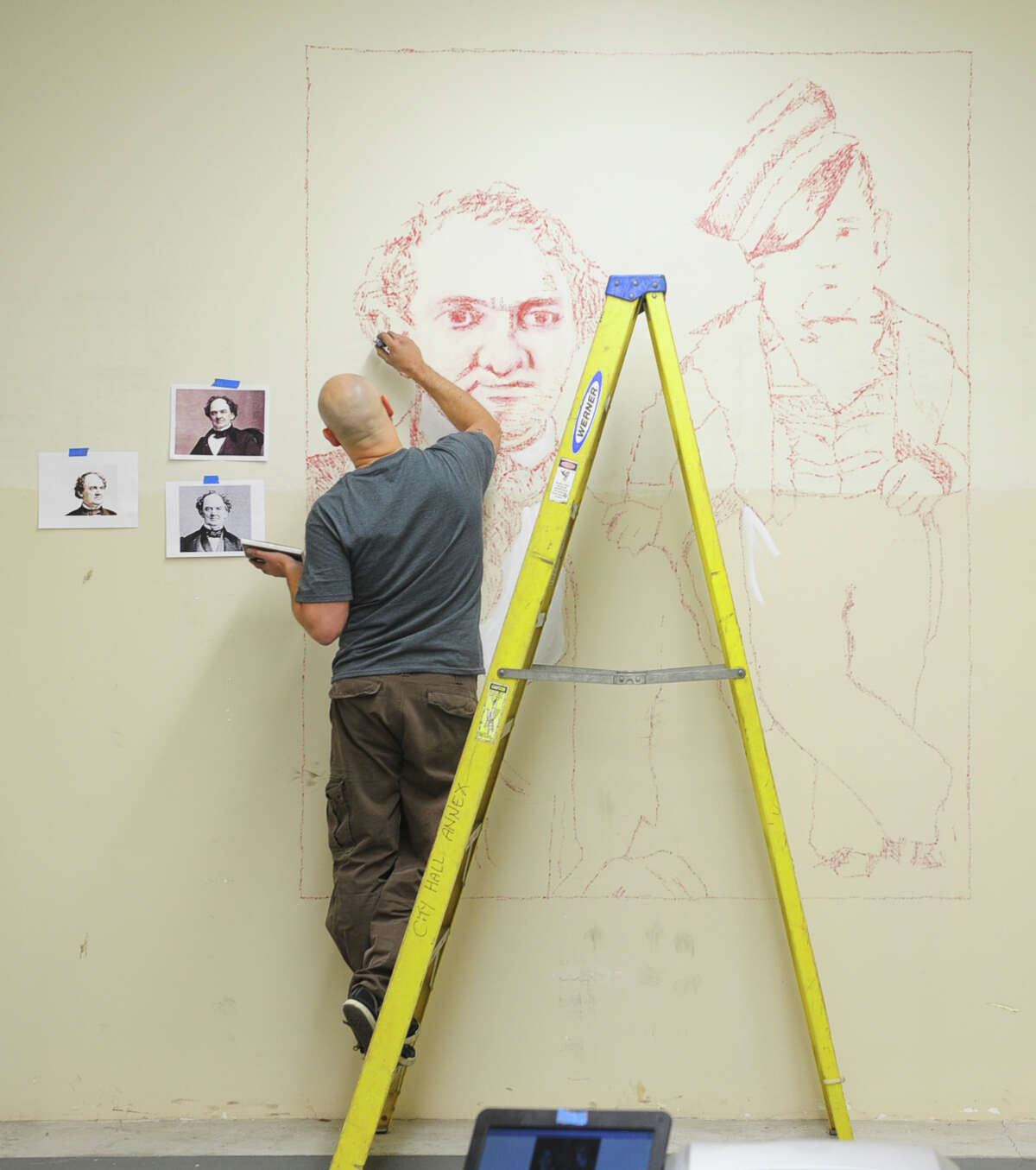 New York artist Roberto Martinez works on a stamp mural of P.T. Barnum and Tom Thumb in the former Probate CourtâÄôs vault Tuesday, Oct. 29, 2013 at McLevy Hall in downtown Bridgeport, Conn. The historic building will become a new home for artists beginning on Nov. 7 thanks to a state-city grant-funded partnership that will provide space for artists to create and sell their artwork from inside the building.