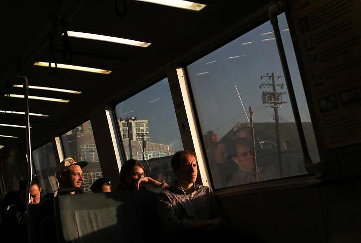 Justin White (right) listens to his headphones while riding on a San Francisco bound BART train in Oakland, Calif. on Friday, Nov. 1, 2013.