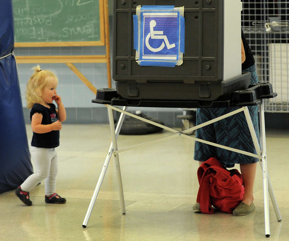 Alison Cassidy waits while her mom, Nicole Cassidy, casts her vote at Black Rock School in Bridgeport, Conn. on Tuesday Sept. 10, 2013. Among the primary races were placed on the ballot for the Bridgeport Board of Education. Those seats are on the ballot in this Tuesday's election. Photo: Cathy Zuraw / Connecticut Post