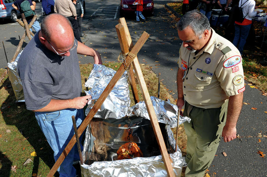 Boy Scout Scout leaders Brian Rapillo, left, and Andy Spalla, with Troop 68 in Trumbull, check on one of three turkeys cooking at Beardsley Zoo in Bridgeport, Conn. on Saturday November 2, 2013. About 30 scouts and cub scouts were at the zoo taking part in an annual service project, in this case, taking apart the zoo's Halloween maze. The turkeys are for a Thanksgiving dinner prepared by the scouts for later in the evening. Photo: Christian Abraham / Connecticut Post
