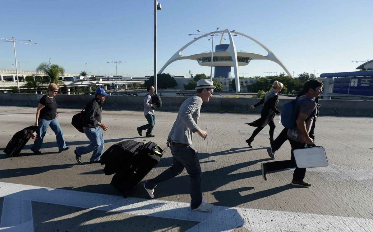 People run towards Terminal 2 at Los Angeles International Airport on Nov. 1, 2013, after the terminal was reopened. A gunman armed with a semi-automatic rifle opened fire at the airport on Friday, killing a Transportation Security Administration employee and wounding others. (AP Photo/Gregory Bull)