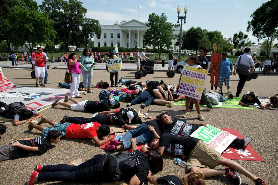 Protesters lay down in front of the White House during a demonstration to signify family members deported, as they rallied in favor of immigration reform. Photo: Evan Vucci, STF / AP
