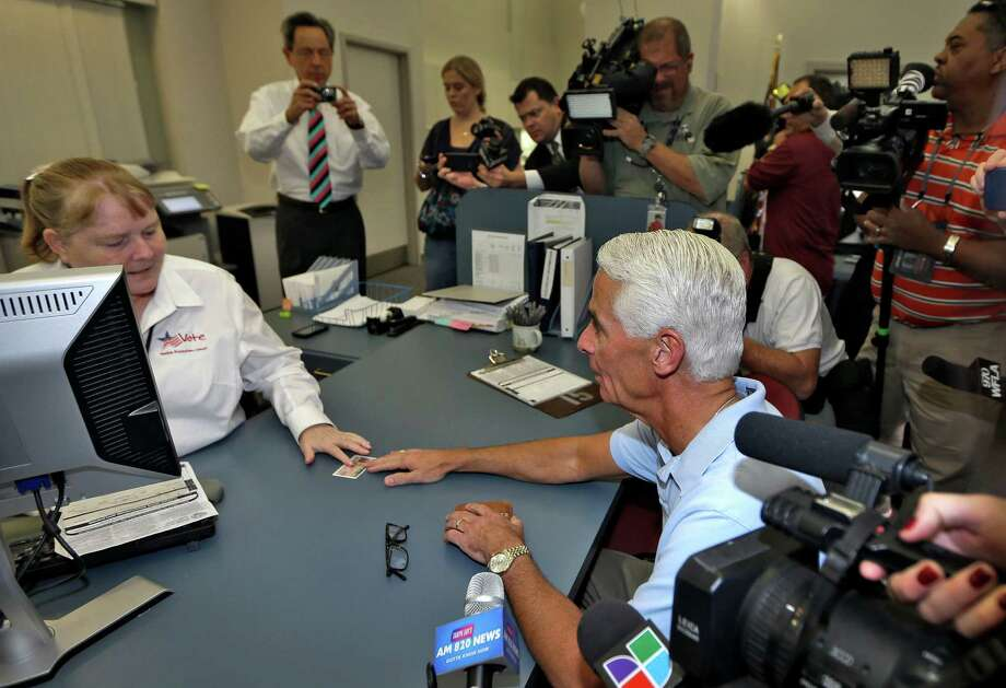Former Republican Florida Gov. Charlie Crist submits his driver's license last December as he became a Democrat. He is running against Gov. Rick Scott. Photo: Chris O'Meara, STF / AP