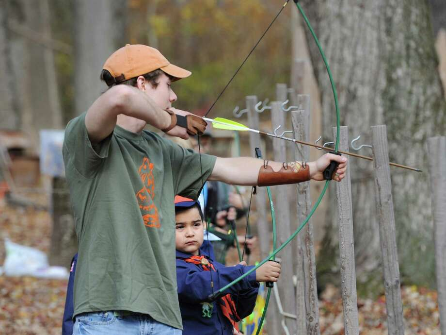 "Boy Scout archery instructor, Jack Smith of Rye, N.Y., left, gives an archery lesson to Greenwich Boy Scout Kevin Barrios, 6, during the Greenwich Scouts ""Turkey Shoot"" event at Seton Scout Reservation in Glenville, Saturday, Nov. 2, 2013. Photo: Bob Luckey / Greenwich Time"