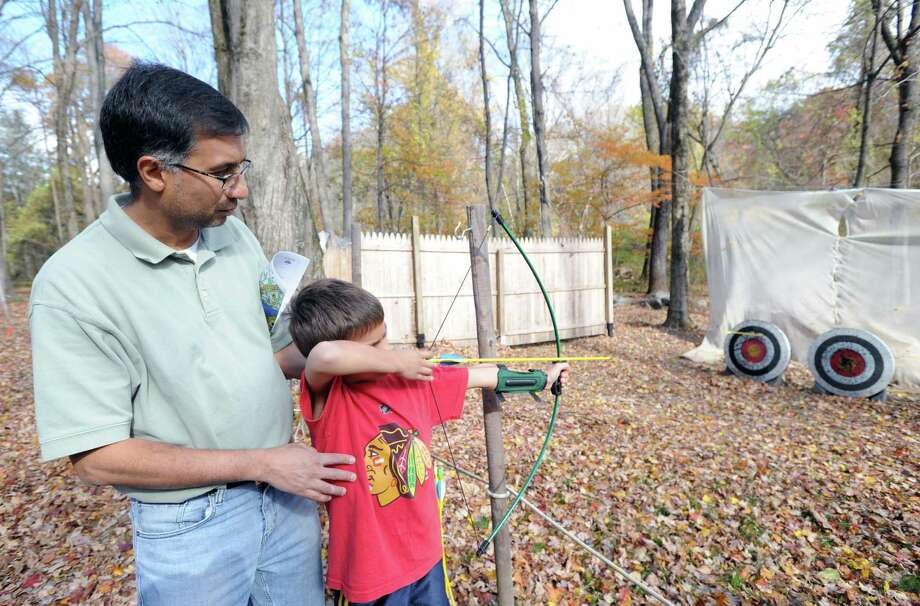 "Bear Scout Arjun Kishore, 8, gets help aiming a bow and arrow from his father, Ashish Kishore, left, during the Greenwich Scouts ""Turkey Shoot"" event at Seton Scout Reservation in Glenville, Saturday, Nov. 2, 2013. Photo: Bob Luckey / Greenwich Time"