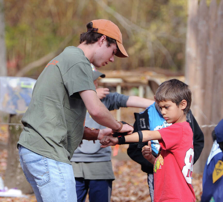 "Boy Scout archery instructor, Jack Smith of Rye, N.Y., left, helps Bear Scout Arjun Kishore, 8, of Greenwich, with a piece of archery gear during the Greenwich Scouts ""Turkey Shoot"" event at Seton Scout Reservation in Glenville, Saturday, Nov. 2, 2013. Photo: Bob Luckey / Greenwich Time"