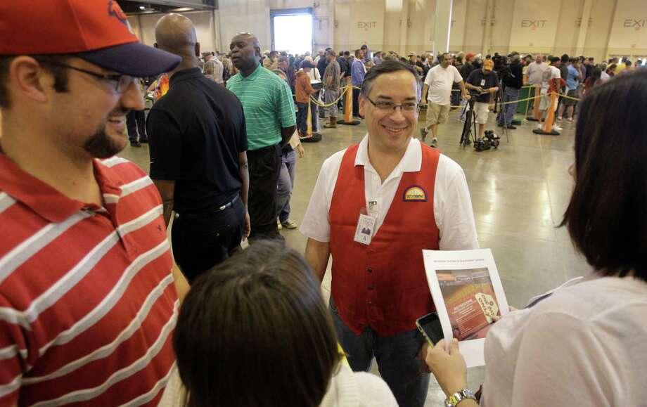 Edgar Colon, center, chairman of Harris County Sports Convention Corp., offers directions to Eric Hermis, left, his wife, Kimberly Hermis, right, during auction and sale of Astrodome items at Reliant Center Saturday, Nov. 2, 2013, in Houston. Photo: Melissa Phillip, Houston Chronicle / © 2013  Houston Chronicle