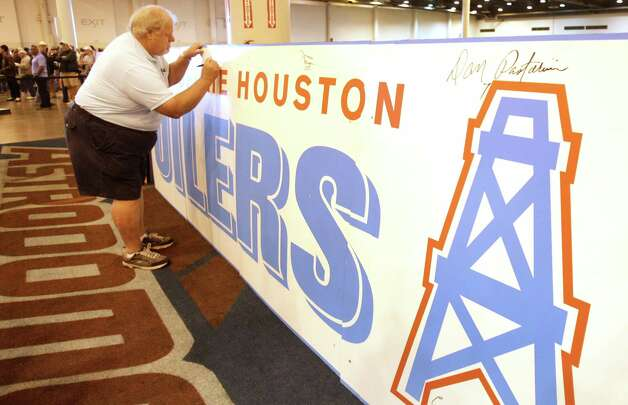 Houston Oilers player John Schuhmacher autographs a replica Oilers sign during the auction and sale of Astrodome items at Reliant Center Saturday, Nov. 2, 2013, in Houston. The sign was a replica  made for the movie Friday Nights Lights that was filmed in the Astrodome. Photo: Melissa Phillip, Houston Chronicle / © 2013  Houston Chronicle