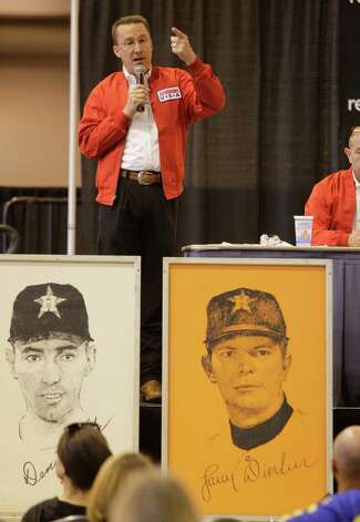Prints of Astros players Denis Menke, left, and Larry Dierker, right, are shown among other prints of players as auctioneer David Runte talks to buyers before auction of Astrodome items at Reliant Center Saturday, Nov. 2, 2013, in Houston. Photo: Melissa Phillip, Houston Chronicle / © 2013  Houston Chronicle