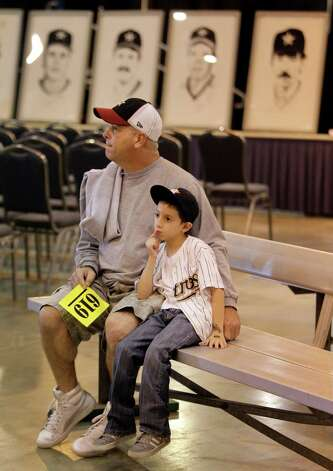 Joe Husband and his grandson, Steven Berlanga, 7, sit on an Oilers sideline bench as they wait for auction of Astrodome items at Reliant Center Saturday, Nov. 2, 2013, in Houston. Prints of Astros player are shown in the background. Photo: Melissa Phillip, Houston Chronicle / © 2013  Houston Chronicle
