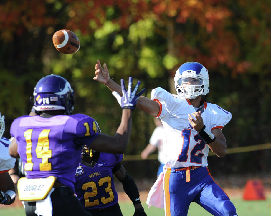 Westhill's Chianta Holtzclaw (# 14) pressures Danbury quarterback Anferny Ith (# 12), right, during the second quarter of the High school football game between Westhill High School and Danbury High School at Westhill High School in Stamford, Saturday, Nov. 2, 2013. Photo: Bob Luckey / Greenwich Time