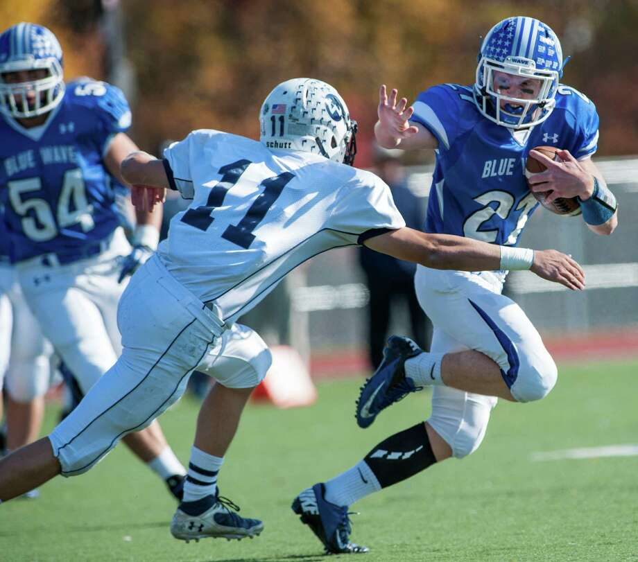 Wilton high school's Brett Phillips tries to tackle Darien high school running back Nicholas Lombardo during a football game played at Darien high school, Darien, CT on Saturday, November, 2nd, 2013. Photo: Mark Conrad / Stamford Advocate Freelance