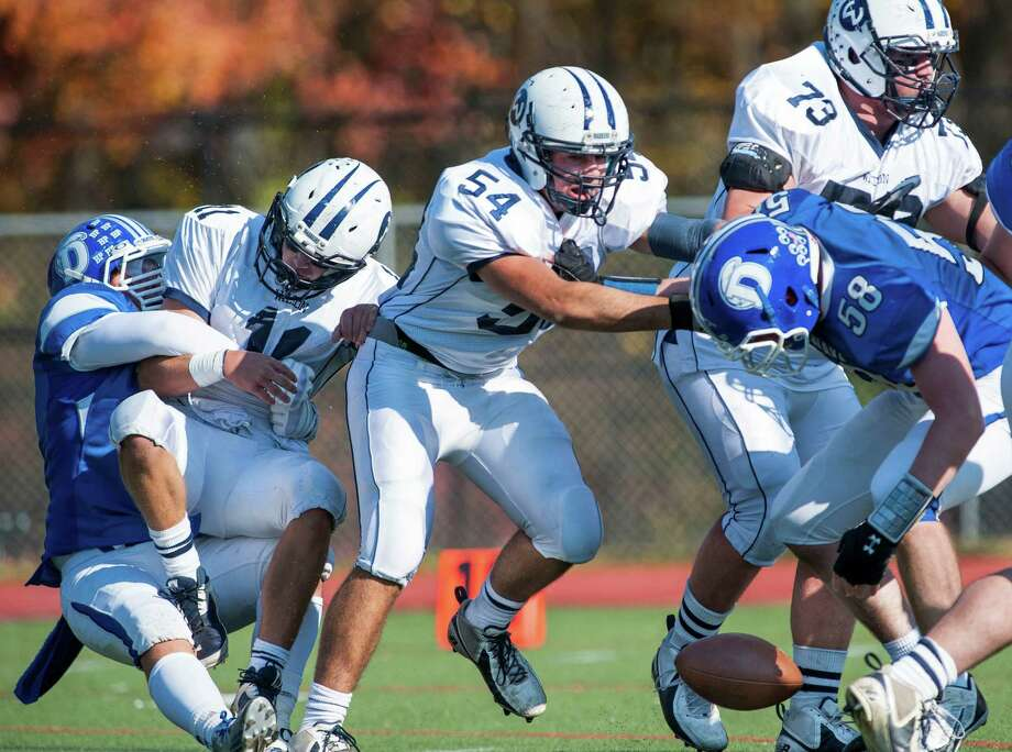 Darien high school's George Reed (left) sacks Wilton high school quarterback Brett Phillips causing him to fumble the ball during a football game played at Darien high school, Darien, CT on Saturday, November, 2nd, 2013. Photo: Mark Conrad / Stamford Advocate Freelance