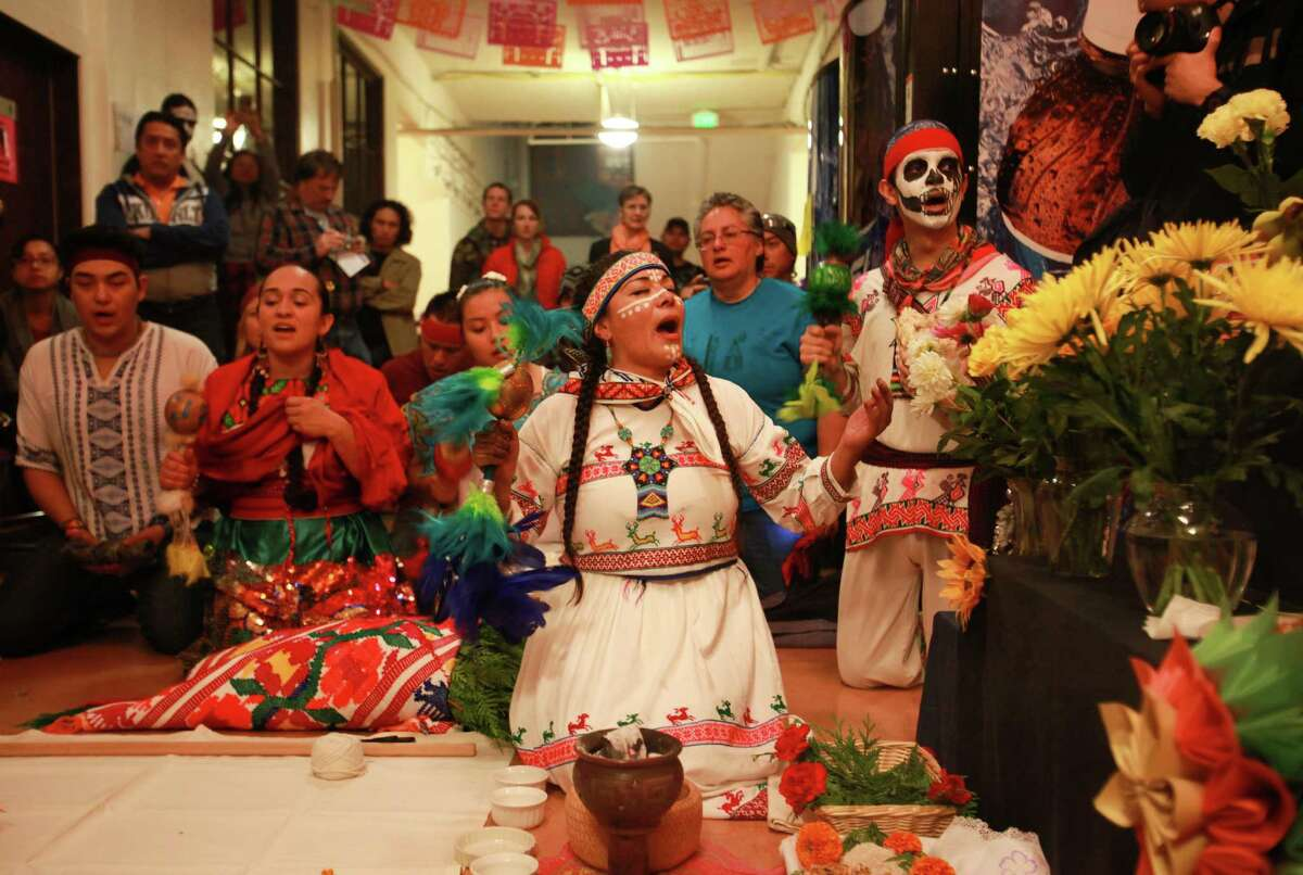Araceli Jaime performs a traditional Aztec ritual to give prayer and offerings at the 9th annual Dia de los Muertos event at El Centro de La Raza on Friday, Nov. 1, 2013. Dia de Los Muertos is a traditional Mexican holiday dedicated to honoring deceased family members.