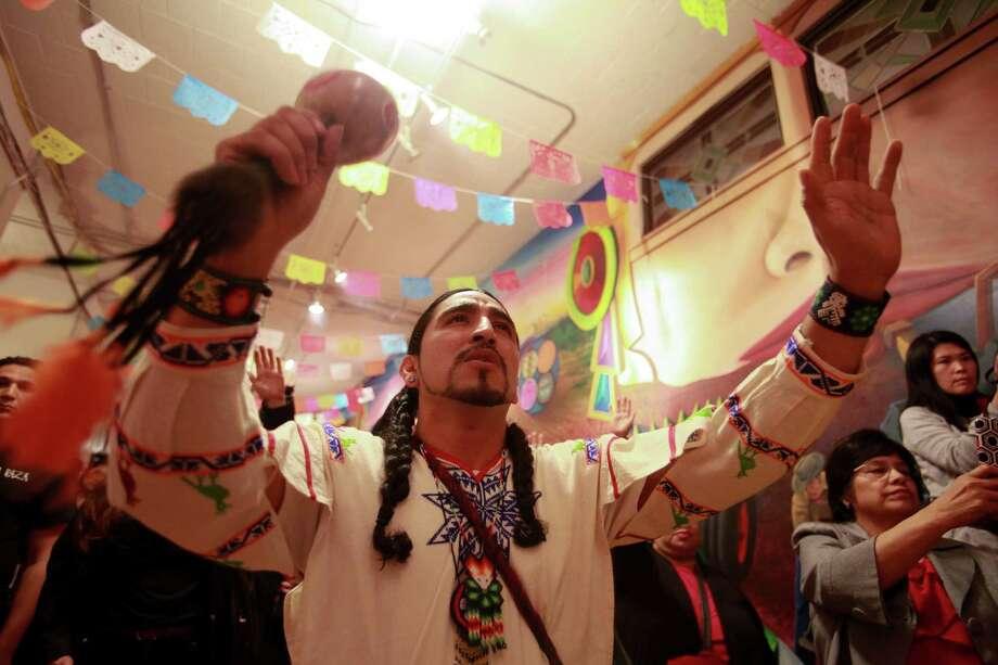 A member of The Ce atl Tonalli dance group performs a traditional Aztec ritual in front of a shrine dedicated to Roberto Maestas, the founder of El Centro de La Raza, at the 9th annual Dia de los Muertos event at El Centro de La Raza. Photo: SOFIA JARAMILLO, SEATTLEPI.COM / SEATTLEPI.COM