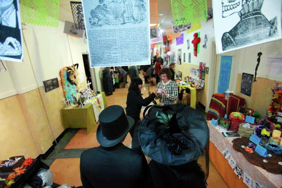 A man and a woman wear Dia de Los Muertos costume hats at the 9th annual Dia de los Muertos event at El Centro de La Raza. Dia de Los Muertos is a traditional Mexican holiday dedicated to honoring deceased family members. Photo: SOFIA JARAMILLO, SEATTLEPI.COM / SEATTLEPI.COM