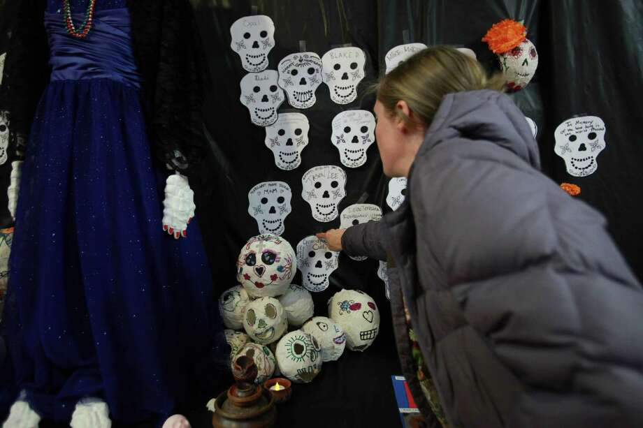 A woman places a paper skull on an offering in honor of a loved one at the 9th annual Dia de los Muertos event at El Centro de La Raza. Dia de Los Muertos is a traditional Mexican holiday dedicated to honoring deceased family members. Photo: SOFIA JARAMILLO, SEATTLEPI.COM / SEATTLEPI.COM