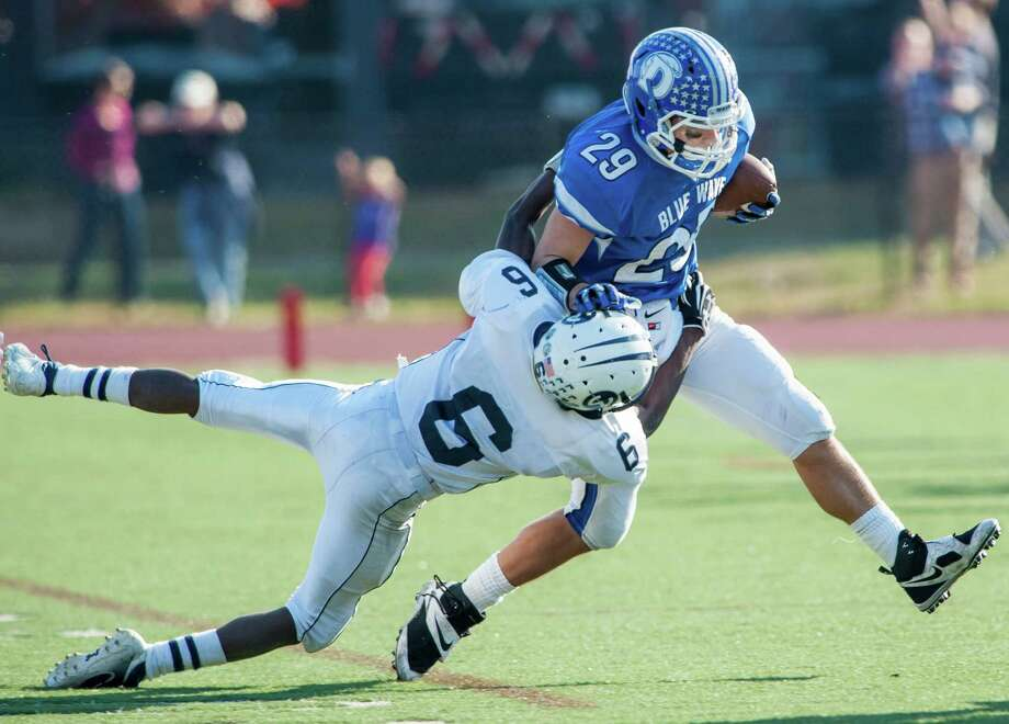 Wilton high school's Rod-Djaly Thoby tries to bring down Darien high school's Myles Ridder during a football game played at Darien high school, Darien, CT on Saturday, November, 2nd, 2013. Photo: Mark Conrad / Stamford Advocate Freelance