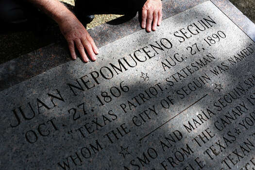 Albert Seguin Gonzales, of Texas City, touches the monument at the burial site of his fourth great grandfather Alamo defender Juan Seguin in Seguin on Oct. 3, 2013. Photo: Lisa Krantz, San Antonio Express-News / San Antonio Express-News