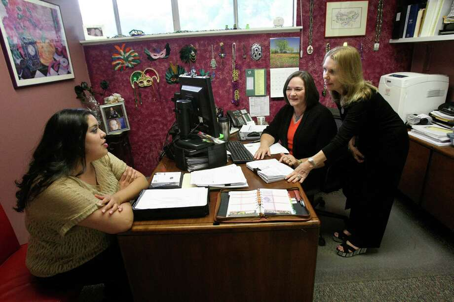 Xochitl Medin speaks with Lynn Rangel and Pamela Bain at Bain Medina Bain, a surveying and civil engineering firm.  The company, with 48 full-time employees and four interns, would have faced a 50 percent increase in their premiums this year if they had stayed with the Aetna policy, so they will be switching to a United Health Care policy on Friday (Nov. 1). President and co-owner Pamela Bain said the company has dodged a bullet for now, but she's apprehensive about what next year will bring. The firm has a number of employees who have been there for decades, so they have an older workforce. Photo: Helen L. Montoya, San Antonio Express-News / ©2013 San Antonio Express-News